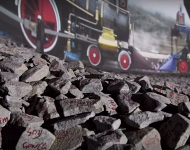 """Zhi LIN, """"Chinaman's Chance"""" on Promontory Summit: Golden Spike Celebration, 12:30 PM 10th May 1869, 2013. HD video projection and painted granite ballast with a surround sound environment. Courtesy of the artist and Koplin Del Rio Gallery, Seattle."""