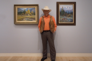 Artist Fred Oldfield wearing cowboy attire standing between two of his paintings of western american landscapes.
