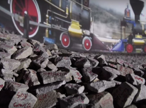 """Zhi LIN, """"Chinaman's Chance"""" on Promontory Summit: Golden Spike Celebration, 12:30 pm, 10th May 1869, 2013. HD video projection and painted granite ballast with a surround sound environment. Courtesy of the artist and Koplin Del Rio Gallery, Seattle."""