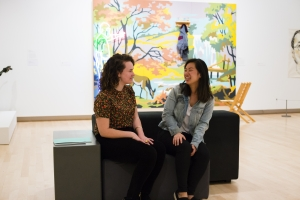 Two visitors chatting while sitting on a bench in the gallery. Behind them is a colorful work of art hanging on the wall.
