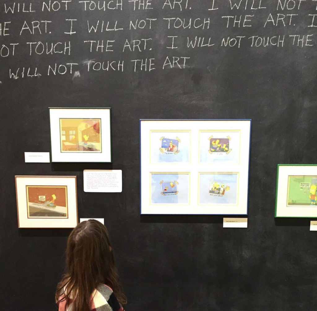 A small child looks up at works on view in Bart at TAM: Animating America's Favorite Family.