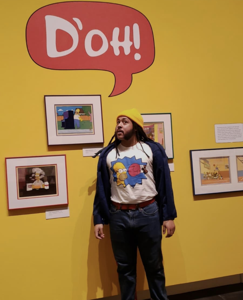 A visitor stands in front of animation cels on view in Bart at TAM: Animating America's Favorite Family.