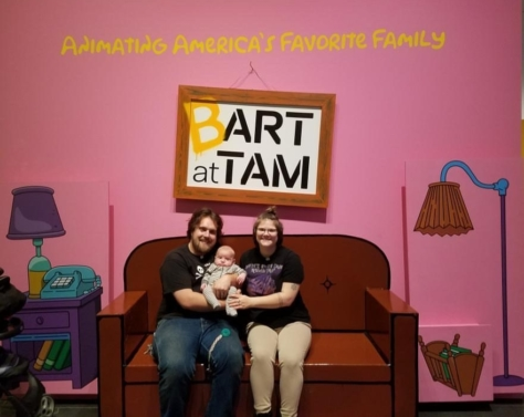 Three people sit on the couch in Bart at TAM: Animating America's Favorite Family.