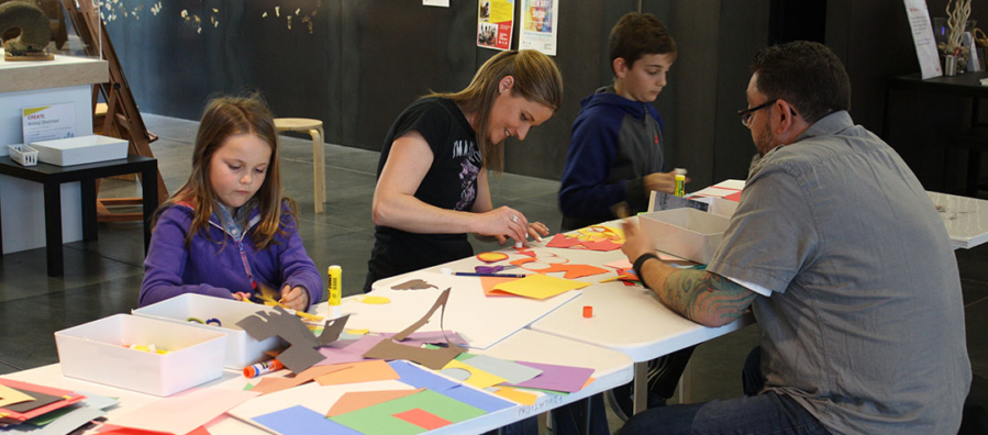 Two adults and two children create art in the museum's art studio.