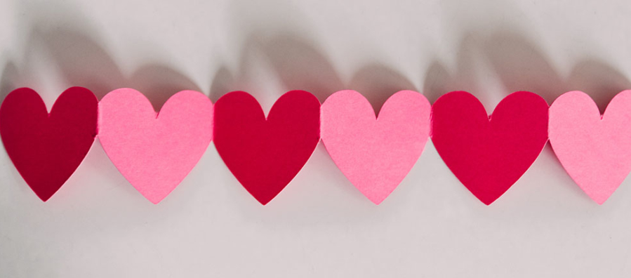 Red and pink paper hearts in line on a white background.