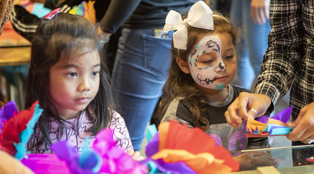 Two children assemble paper flowers during the Dia de los Muertos community festival.