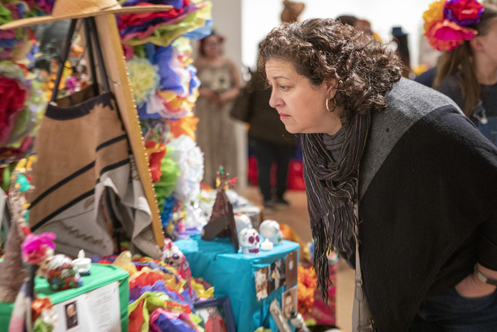 Woman leans over to look closely at an altar set up during TAM's Dia de los Muertos community festival.
