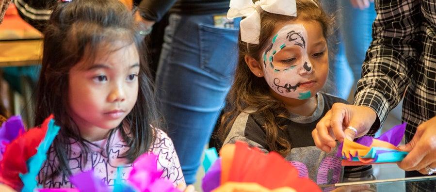 Two children assemble paper flowers during the Dia de los Muertos community festival.