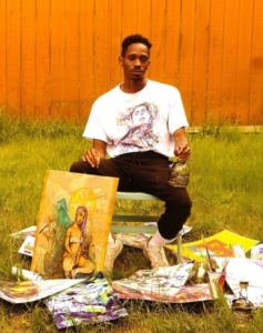 Artist Perry Porter sits in a grassy yard surrounded by his work and painting supplies.