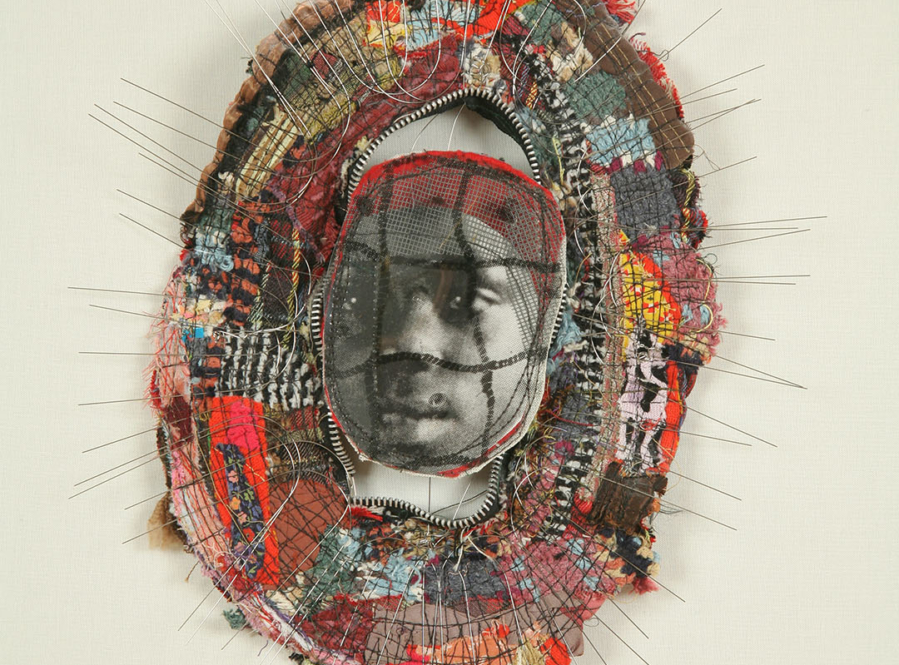 Small brooch-like sculpture with a photo of a young girl at center surrounded by a border of wire and cloth fragments. There is a fence pattern across the girl's face.