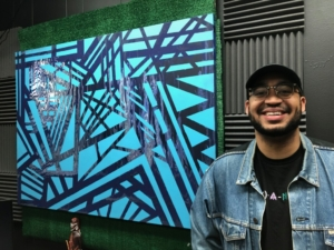 Artist Jalen Calhoun stands in front of an abstract painting he created.