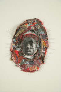 Small brooch-like sculpture with a photo of a young African American girl at center surrounded by a border of wire and cloth fragments.