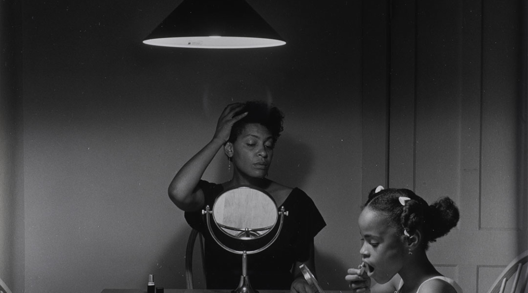 A black and white photography taken by artist Carrie Mae Weems that features a black woman sits at the kitchen table styling her hair while her daughter puts on lipstick next to her.