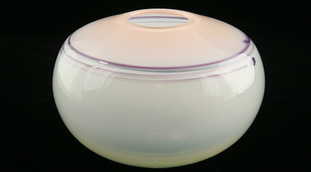 Glass vessel with a white bottom and pink top. Purple lines circle the shoulder