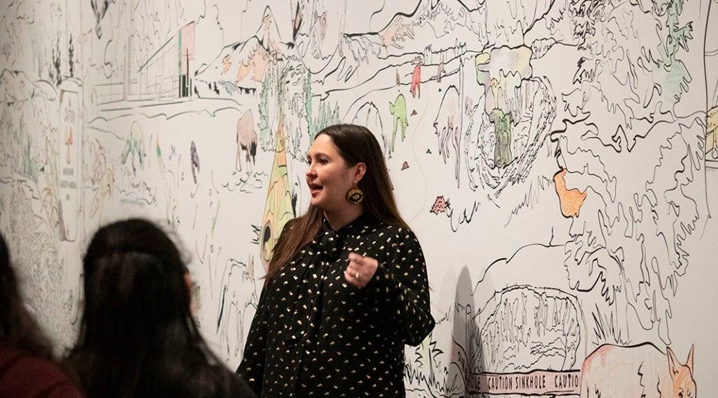 """Artist RYAN! Feddersen standing in front of her mural """"Coyote Now Epic"""""""
