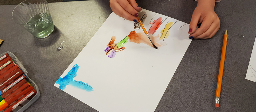 Child completes a painting using watercolors.