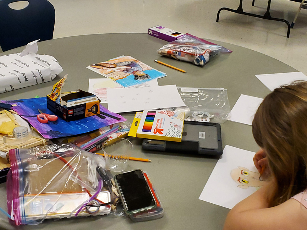 Child drawing amongst art supplies strewn over a table.