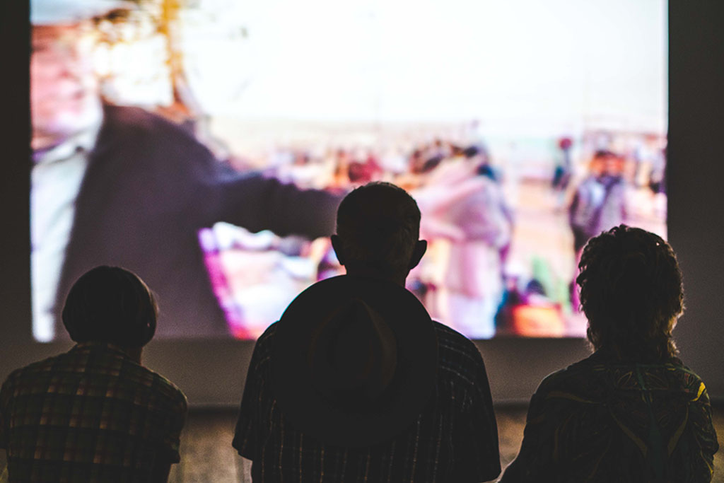 Three people sit in front of a blurry screen. Photo by Aneta Pawlik on Unsplash.