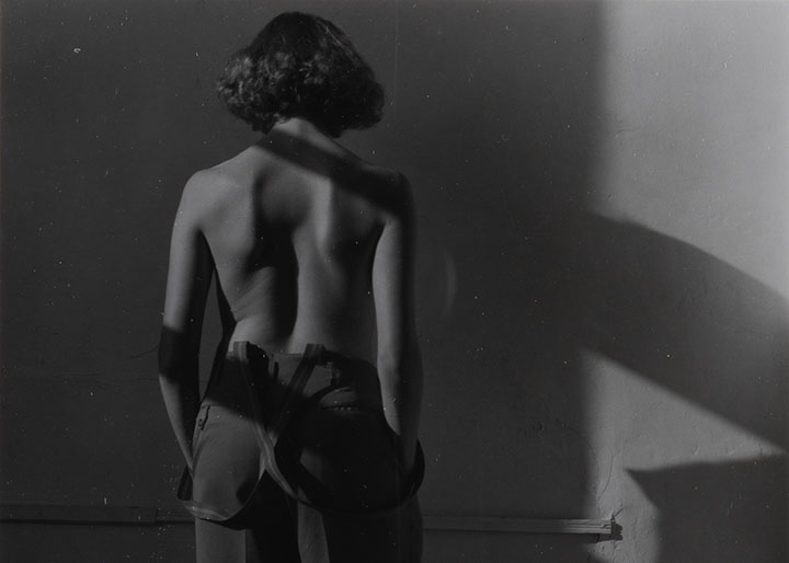 A woman in trousers and suspenders stands facing a wall with her back to the viewer. She is nude from the waist up.