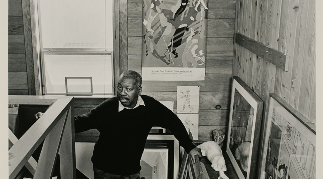 Black and white portrait of the artist, Jacob Lawrence standing on the stairs up to his loft studio.