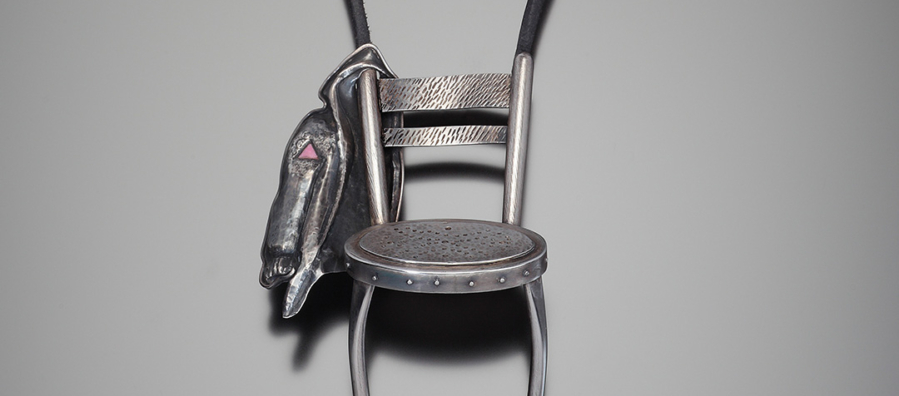 Chair with jacket hanging on proper right side of chair back.