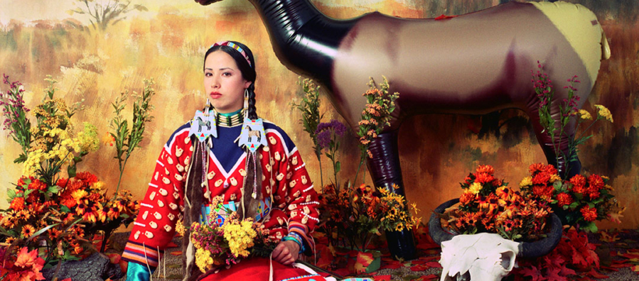 Staged diorama-like image of a woman in a colorful skirt and blouse, wearing elaborate jewelry and hair ornaments holding a feather fan, wildflowers and a beaded bag seated in front of a backdrop painted with an autumn landscape. Leaves scattered on the ground, a plastic elk and an animal skull to her left.