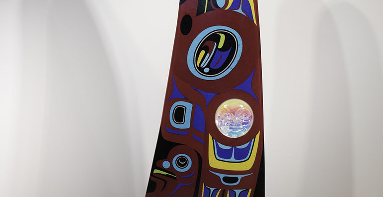 "A large fin-shaped piece of glass with a red background, black top, and base made of blue metal wave shapes. The body of the ""fin"" is decorated with Native American designs in blue, yellow, red, black and white. A glass face is inset into the fin at lower left."