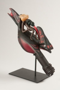 Sculpture of a large, black bird with three figures on its back: a masked human body with a frog-like animal straddling a large bird's (rabbit's?) head. Frog is inserting tongue into bird head's mouth.