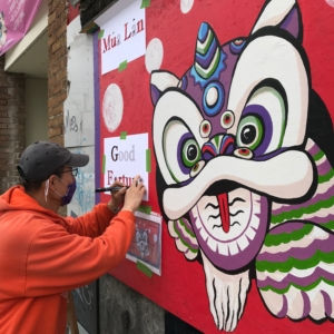 Artist Nori Kimura works on his mural depicting a colorful dragon on a vibrant red background.