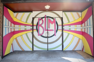 "White panels decorated with green, yellow, and pink concentric circles, lines, and ""BLM"" at the center cover storefront windows."