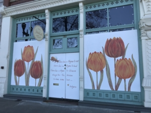 White painted panels decorated with orange and red tulips cover storefront windows