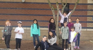 Eleven grade school students stand outside of the school around a tree.