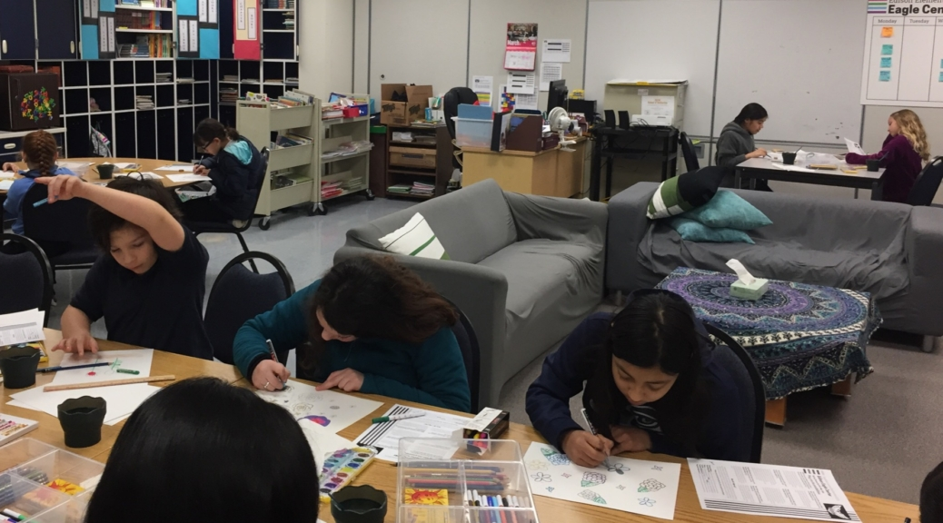 Students sit at tables working on art projects during Sketch Club