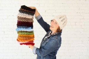 Woman wearing a denim jacket and a knit white hat holds a multicolored stack of knit products.