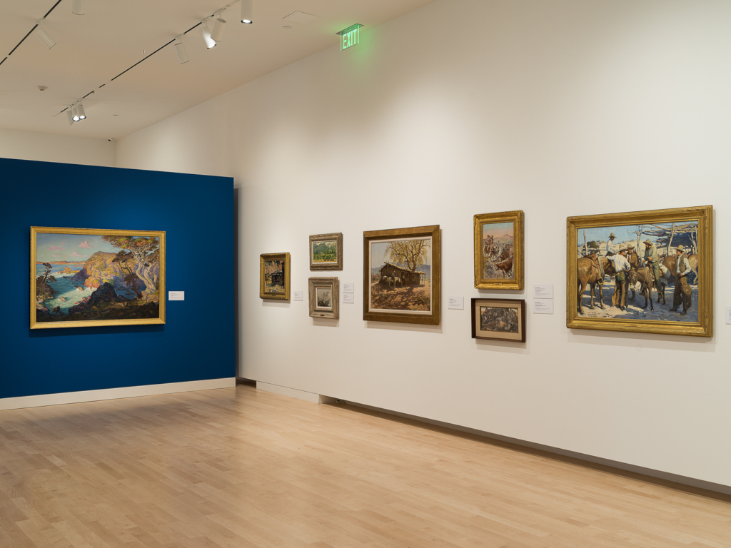 View from Immigrant Artists and the American West featuring 7 paintings hung on a white wall. A bright blue wall with a single painting is perpendicular to the white wall.