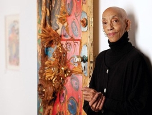 Artist Aminah Robison pictured in a gallery with one of her artworks