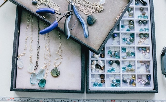 Photo of jewelry making tools, collection of loose gemstones, and finished necklaces.