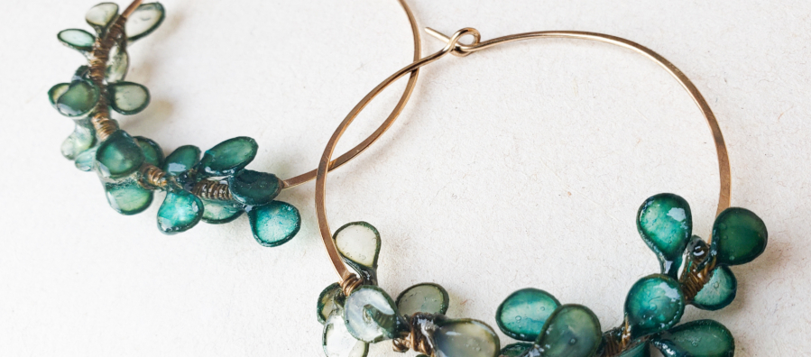 Photograph of large hoop earrings decorated with blue-green leaf-like shapes