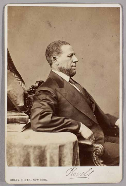 Black and white photograph of Senator Hiram Rhodes Revels seated in profile.