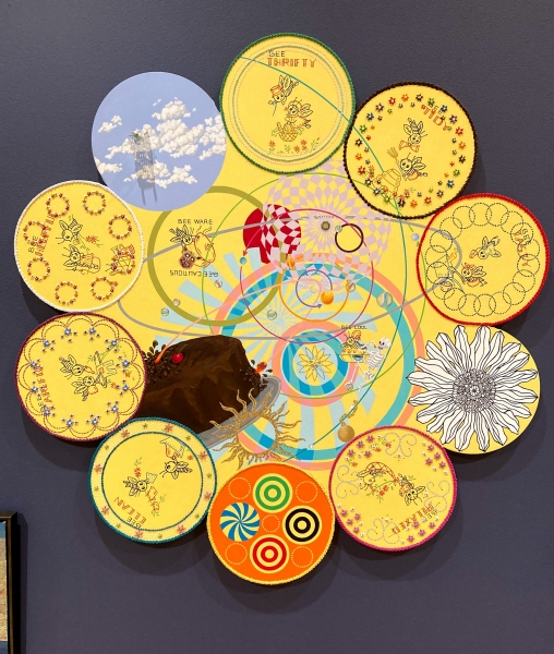 Artwork is composed of a large central circular canvas with a border of smaller circular canvases. All are painted with symbols and geometric shapes against a yellow background.