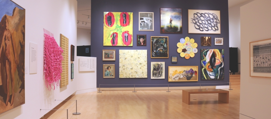 Photograph of a museum gallery space with a salon-style wall where 16 paintings are hung on a dark grey wall.