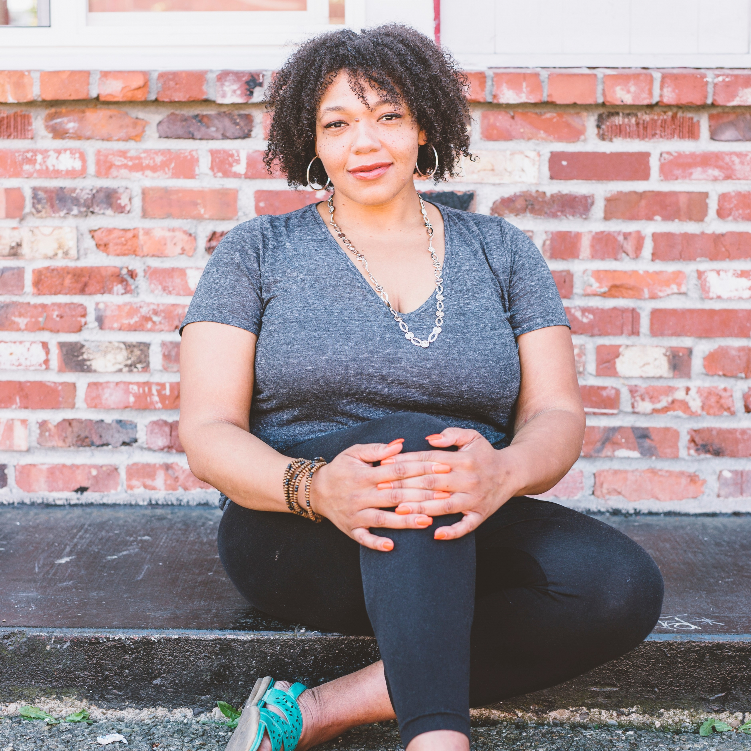 Photo of SWASH Body owner and CEO Aikita Jones posed seated on the sidewalk in front of a brick wall.