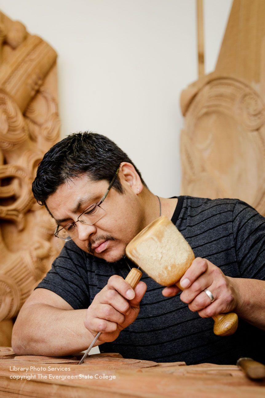 Photo of artist Alexander McCarty in the process of carving a sculptural piece.