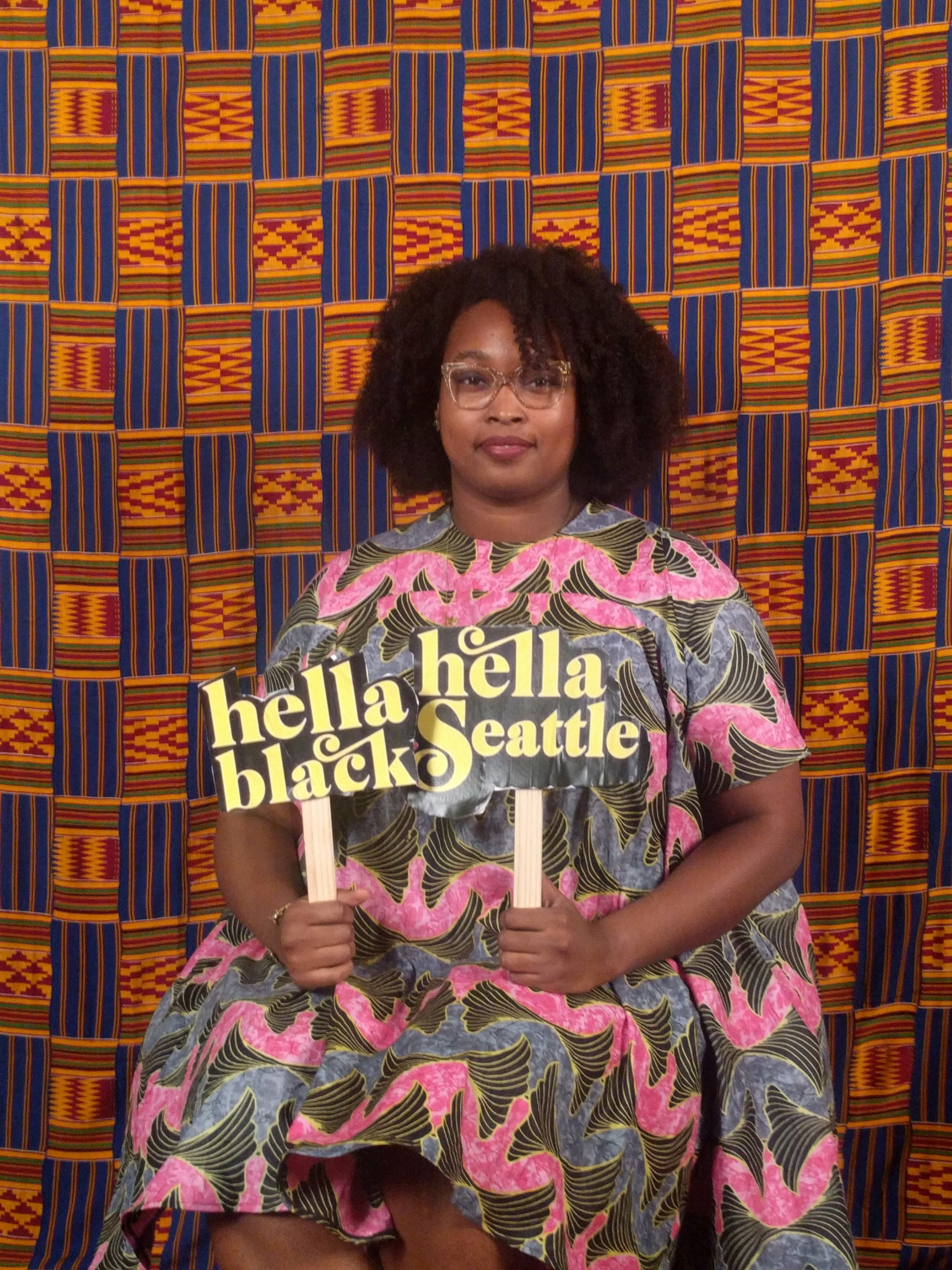 Color photograph of Seattle artist, the monarq posed in front of a quilted background.