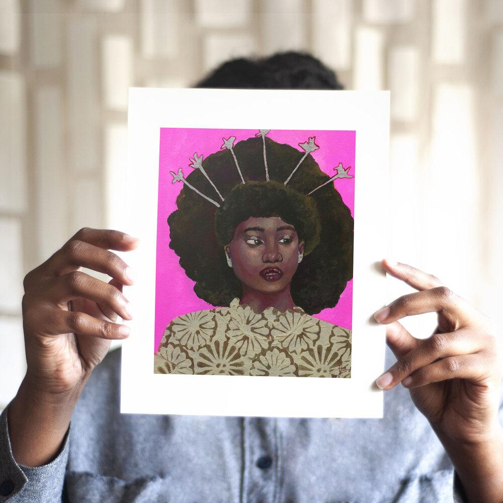 Color photo of figure holding up print by Seattle artist, the monarq.